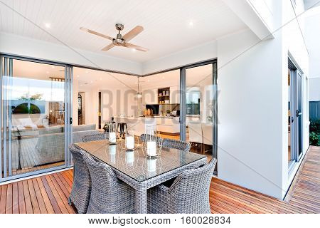 Outdoor patio area with table set up beside an entrance to inside of a modern house with a kitchen there are candles on the table under the fan