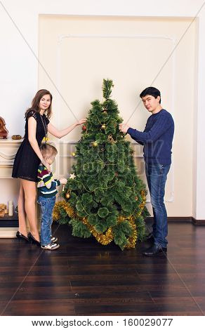 family, x-mas, winter holidays and people concept - mother, father and child decorating christmas tree at home.