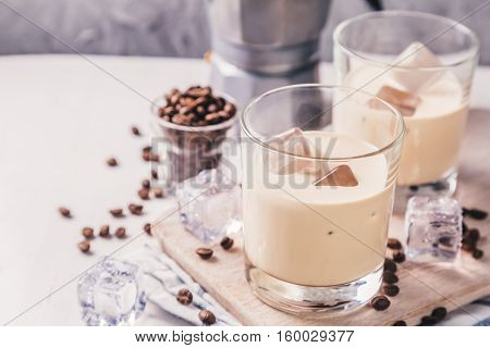 Coffee liqueur in glasses with ice and beans, wood background, copy space, toned