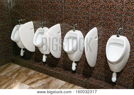 white urinals on a brown background glazed tiles in the men's room