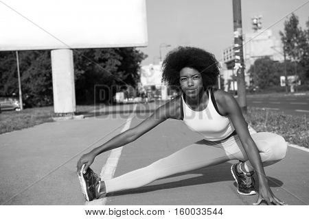 portrait of a young beautiful African American girl doing stretching beautiful summer morning on the streets of the city