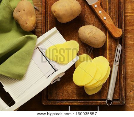 Peeled and sliced raw potatoes on a cutting board