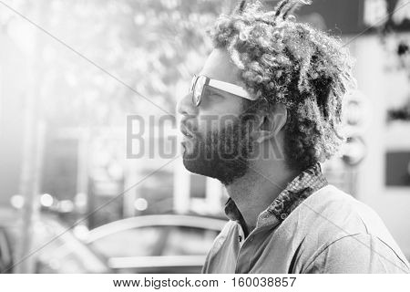 Portrait of young black man with dread locks wearing sunglasses. Black and white effect applied.