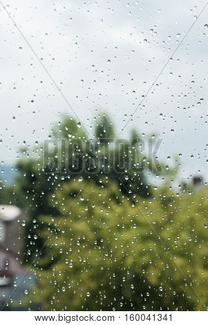Raindrops Od Window Glass With Trees And City As Background