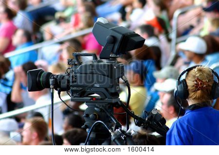Commercial Videographer With Camera In Clear Focus And Audience