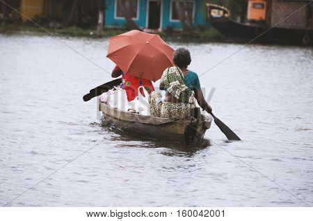 Asian people travel by a boat on a river