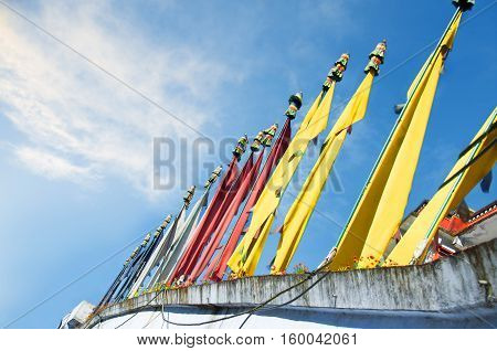 Tibetan prayer flags pyllons  at a blue sky