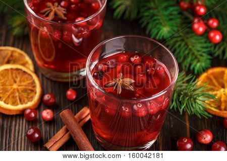 Two glasses of cranberry drink, cranberries, cinnamon sticks, anise stars and dried slices of orange on a wooden background. Close up