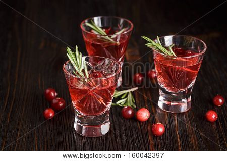 Christmas refreshing alcoholic drink with cranberries and rosemary on wooden background, with fir branches