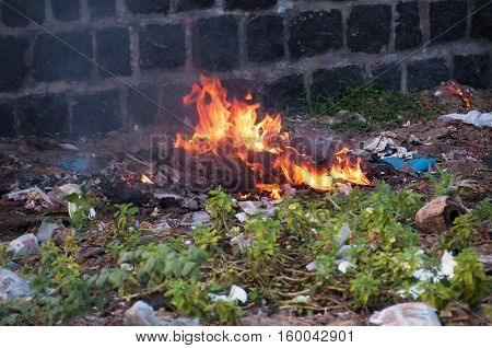 Burning plastic trash on illegal landfill burning