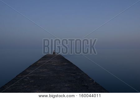 young girl sitting on the edge of the pier in the lotus position she breathes the sea air and enjoy the silence