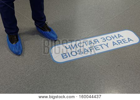 ST. PETERSBURG, RUSSIA - NOVEMBER 16, 2016: Media representative in shoe covers at the entrance to the biosafety area during the press tour to the biotechnology company BIOCAD