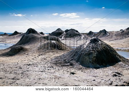 Field with craters of mud volcano in Gobustan and eruption bubbling mud. Azerbaijan.