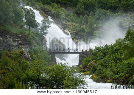 Tourists in water shower on the bridge of Briksdalsbreen hike waterfall. Norway popular touristic hike to Briksdal glacier.