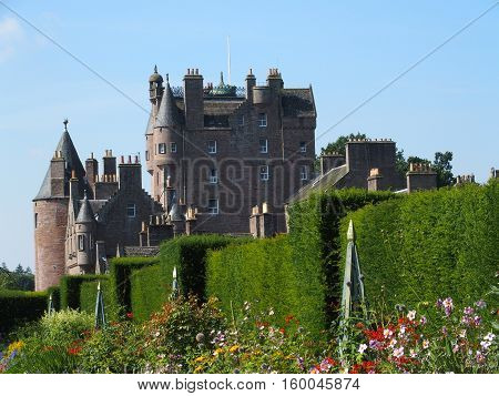 Medieval scottish GLAMIS castle and flowers in garden with clear blue sky in sunny and warm summer day, SCOTLAND, GREAT BRITAIN UK, AUGUST 2016.