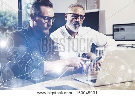 Concept of digital screen, virtual connection icon, diagram, graph interfaces.Bearded young man using mobile phone.Adult colleague working together with partner.Film effect, flare