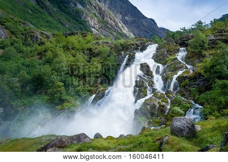 Briksdalsbreen waterfall. Norway national park and popular hiking path to glacier viewpoint.
