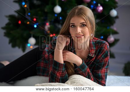 Portrait of happy beautiful girl on bed at home with decorated Christmas tree in background