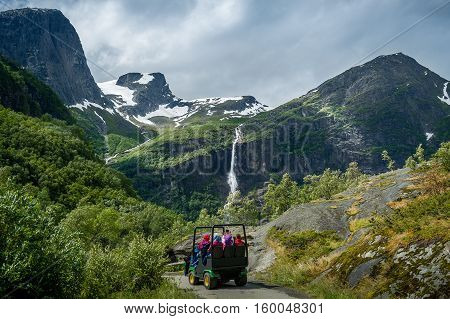 Group of tourists in the special excursion troll car on it's way to Briksdalsbreen glacier viewpoint. Briksdal, Norway