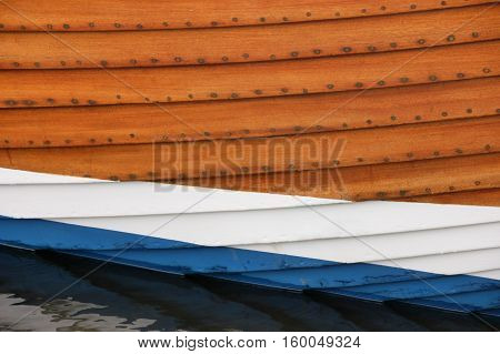 Close up view of the hull of a clinker built fishing boat with varnished and painted planks of white and blue
