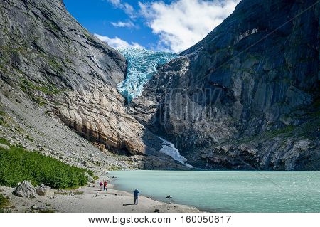 Tourists at Briksdalsbreen glacier viewpoint. Rocky mountains, melted ice lake and gravel beach. Popular travel destination of Norway.