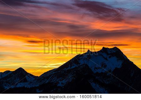 Red and orange sunset silhouettes a mountain peak