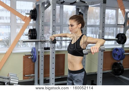 Beautiful fitness woman with lifting dumbbells . Sporty woman lifting light weights. Fit girl exercising building muscles. Fitness and bodybuilding.