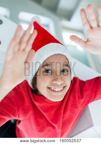 Funny boy hanging down at home with Santa hat