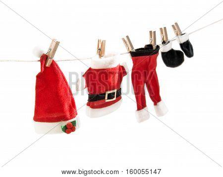 Santa Claus suit hanging on clothesline. Christmas theme. Horizontal.