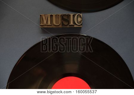 The word music in old metal type with two vinyl recordings on a dark background