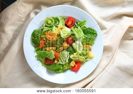 Ovehead view of salad with cherry tomatoes and cornbread