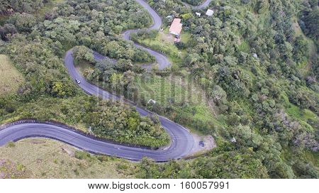 Aerial top view of a rural mountain road full of curves