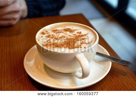 Delicious foamy cappuccino on a white cup on a plate.