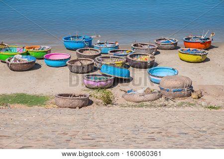 Colorful traditional boats in fishing village Mui Ne Binh Thuan Province Vietnam Southeast Asia. Round basket boats Thung Chai. Sea shore. Popular asian landmark famous destination of Vietnam