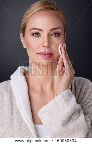 Beautiful nourished woman cleaning skin on  face, concept middle aged people