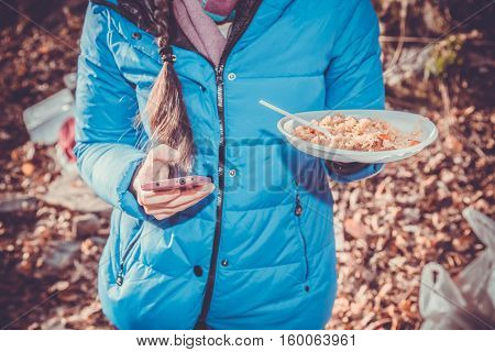Girl eating plov in nature and looks smart.