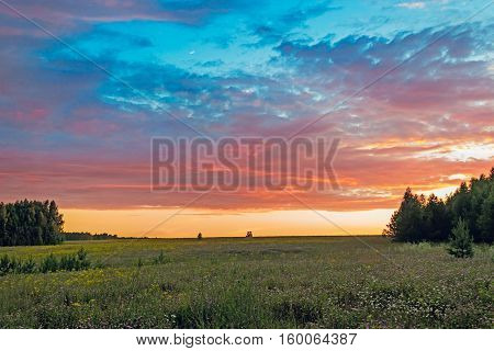 Sunrise in the clouds over the flower meadow
