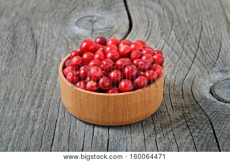 Red lingonberry in wooden bowl on wooden table