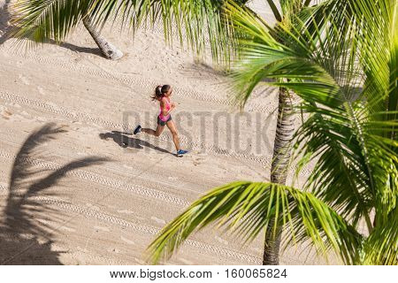Fitness athlete running training cardio on beach. Woman jogging in between palm trees. View from above of the ground and sand. Health and sports concept. Copyspace.