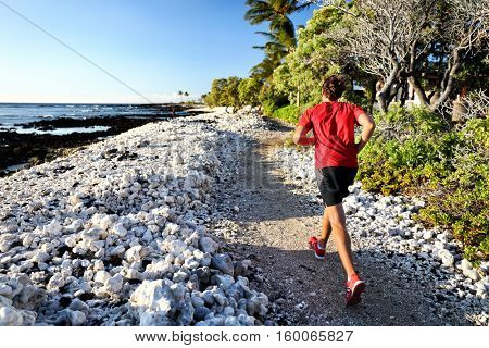 Trail runner jogging on running path at beach in white coral rocks at hawaii travel destination. Male athlete from behind doing cardio exercise outdoors in nature.