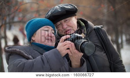 Two senior woman looking to they self photo camera at winter day, outdoor, horizontal