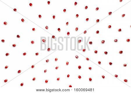 Fruit pomegranate seeds scattered in a chaotic manner, isolated on white background. Food background.