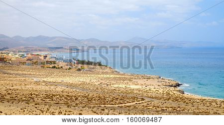 View on one of the best beaches in the world Playa de Sotavento with large sand dunes hotels and mountains on the Canary island Fuerteventura in Spain.