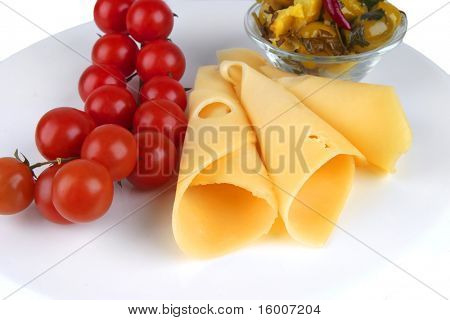 slices of yellow cheese with olives and tomatoes on dish