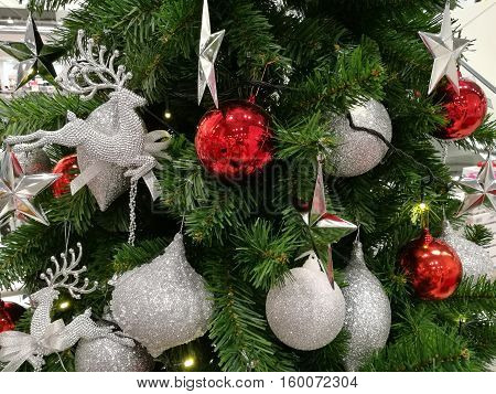 Embellished Christmas tree decoration glitter silver ornaments and red ball (medium shot)