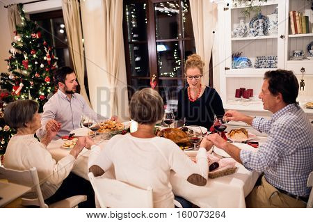 Beautiful big family sitting at the table, celebrating Christmat together at home, holding hands, praying. Illuminated Christmas tree behind them.