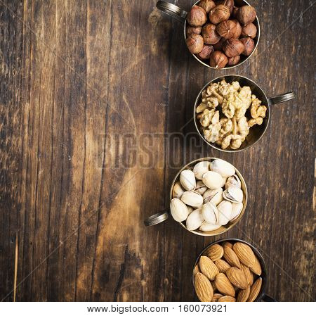Four vintage cupro-nickel cup full of different nuts, almonds, pistachios, walnuts and hazelnuts on a dark wooden background.