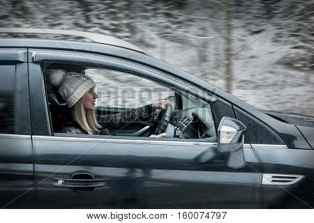 Woman at winter time. Yoyng female sitting and driving in black car at snowly winter day.