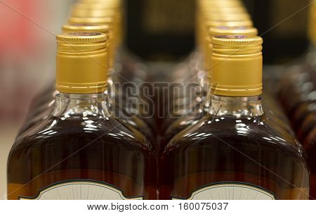 Top of plastic bottles with cognac or brandy standing in the liquor store. From the front