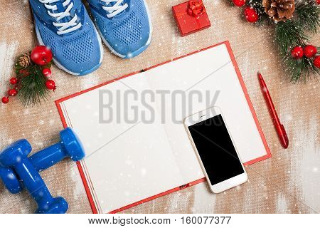 Christmas Sport Composition With Sport Shoes, Dumbbells, Notebook And Smartphone